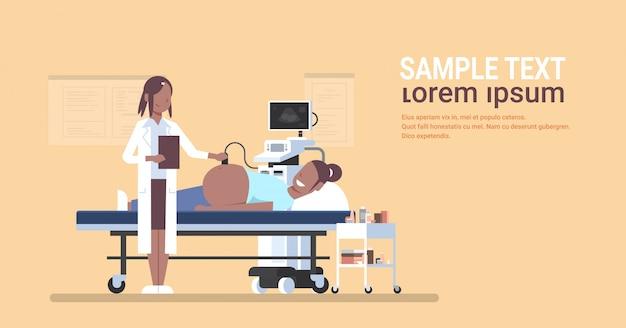 Mujer visitando médico estadounidense afican haciendo ultrasonido cribado del feto en ginecología monitor digital