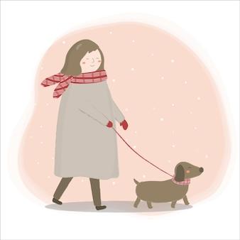 Mujer vistiendo un abrigo paseando al perro