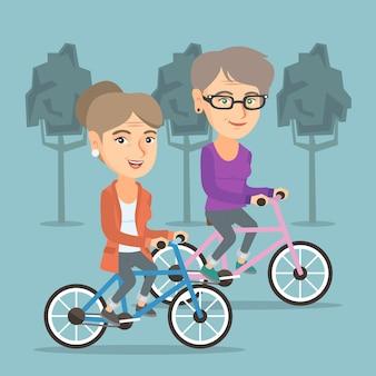 Mujeres caucásicas jubiladas que montan las bicicletas en parque.