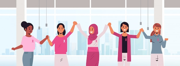 Las mujeres con cintas de color rosa tomados de la mano se mezclan las niñas de raza que se unen día de cáncer de mama conciencia de la enfermedad y el concepto de prevención moderno interior de la oficina retrato plano horizontal