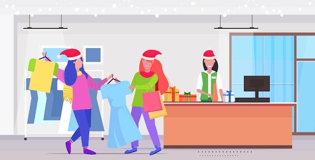 Las mujeres compradoras con gorro de papá noel luchando por el último vestido pareja de clientes en la venta de compras de temporada concepto de lucha moderna boutique de moda interior de longitud completa
