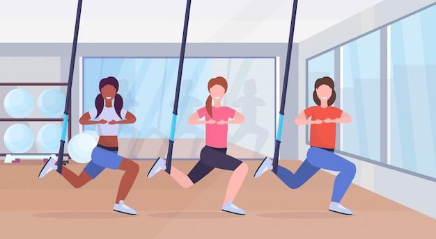 Mujeres deportivas haciendo sentadillas ejercicios con suspensión correas de fitness cuerda elástica mezcla raza niñas entrenamiento crossfit grupo clases entrenamiento concepto moderno gimnasio club de salud interior de cuerpo entero