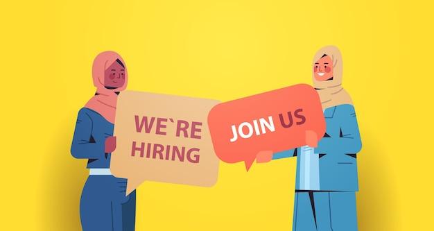 Mujeres empresarias árabes gerentes de recursos humanos que sostienen que estamos contratando únete a nosotros carteles vacante de recursos humanos contratación abierta concepto de recursos humanos retrato horizontal ilustración vectorial