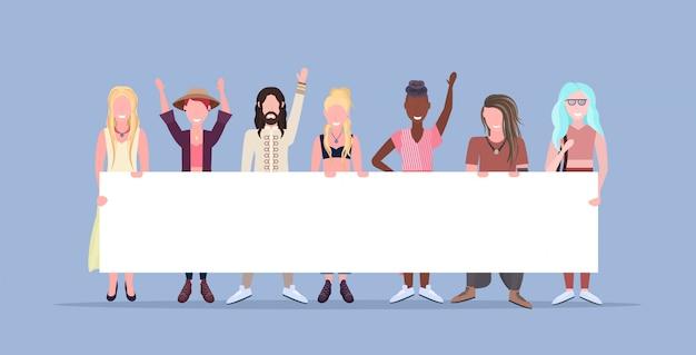 Mujeres felices hombres de pie juntos sonriendo raza mixta personas sosteniendo vacío cartel cartel hembra personajes de dibujos animados masculinos longitud completa fondo azul horizontal