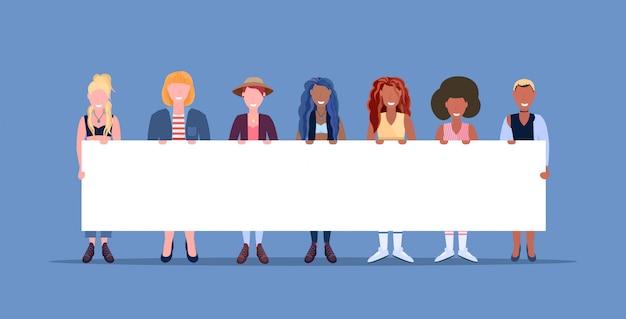 Mujeres felices de pie juntos sonriendo raza mixta niñas sosteniendo carteles vacíos letrero femenino personajes de dibujos animados de fondo azul horizontal