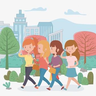 Mujeres hermosas caminando en el parque usando teléfonos inteligentes