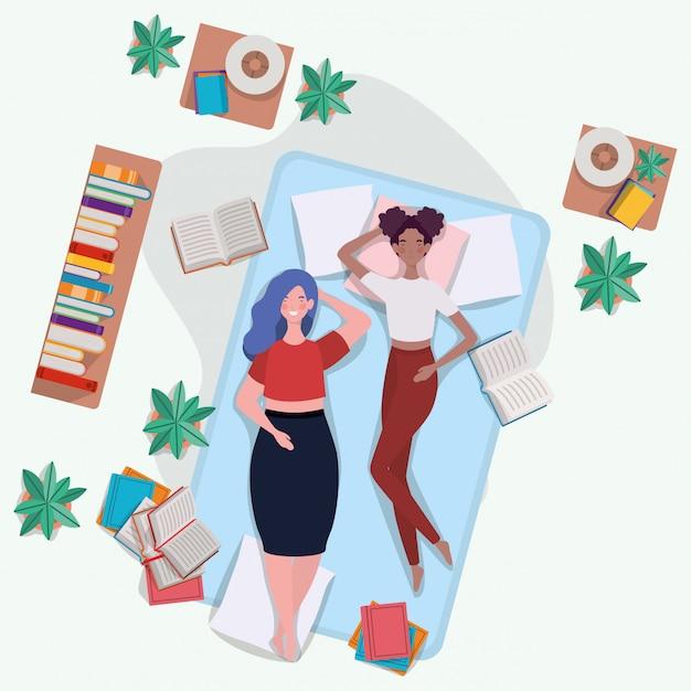 Mujeres interraciales descansando en un colchón en el dormitorio.