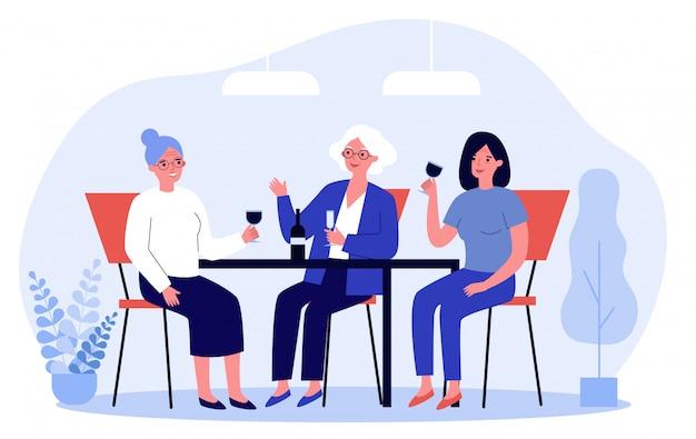 Mujeres jóvenes y mayores bebiendo vino en café