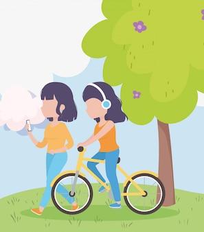 Mujeres jóvenes con teléfono inteligente y bicicleta
