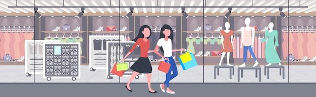 Mujeres llevando bolsas de compras chicas pareja divirtiéndose caminando juntos vacaciones concepto de gran venta boutique moderna tienda de moda exterior banner horizontal de longitud completa