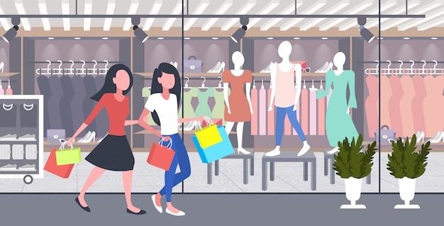 Mujeres llevando bolsas de compras chicas pareja divirtiéndose caminando juntos vacaciones gran venta concepto boutique moderna tienda de moda exterior integral horizontal