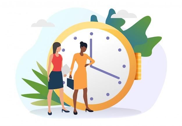 Mujeres de negocios mirando las manecillas del reloj
