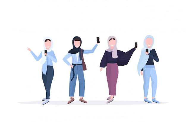 Mujeres con pañuelo en la cabeza tomando una foto selfie en la cámara del teléfono inteligente personajes de dibujos animados femeninos árabes de pie juntos fotografiando fondo blanco horizontal de longitud completa