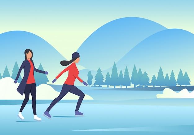 Mujeres patinando sobre hielo con paisaje nevado.