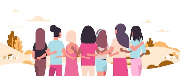 Las mujeres de pie y abrazándose juntas mezclan a las niñas de raza que luchan contra la conciencia del cáncer de mama y la prevención del concepto de paisaje horizontal de fondo vista trasera horizontal