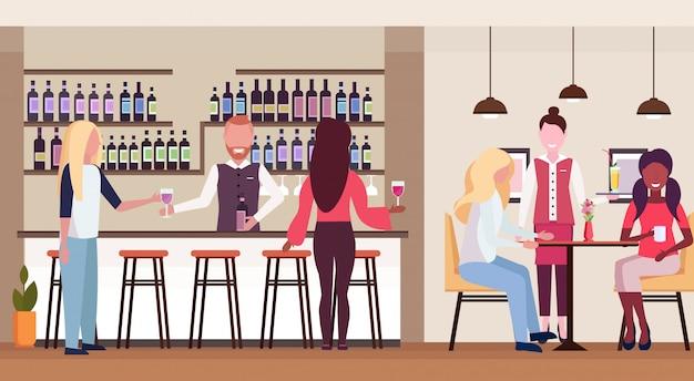 Las mujeres de pie en la barra de bar bebiendo alcohol barman sosteniendo una botella de vino y vidrio barman y camarera sirviendo clientes de raza mixta moderno café interior plano horizontal