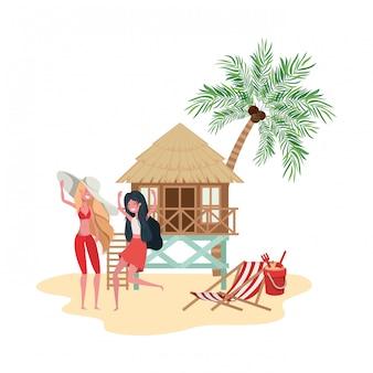 Mujeres de pie en la playa con casa de playa