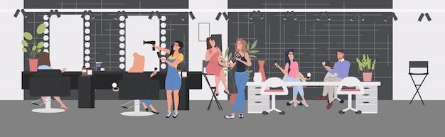 Mujeres probando productos cosméticos peluquería haciendo peinado a clientes que discuten durante la reunión interior moderno salón de belleza de cuerpo entero horizontal