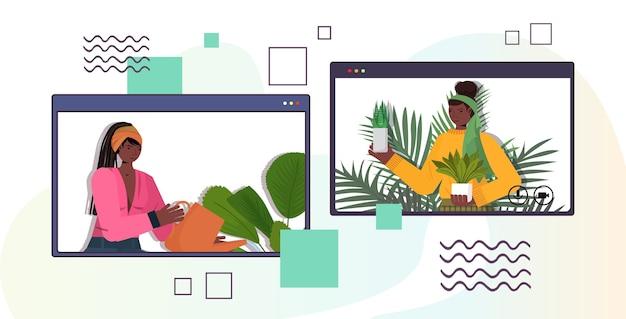 Las mujeres que cuidan de las plantas de interior amas de casa afroamericanas discutiendo durante la videollamada en el navegador web vertical vertical de windows