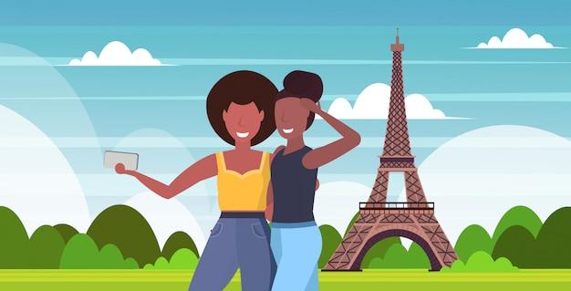 Las mujeres que toman la foto selfie en la cámara del teléfono inteligente mezclar chicas de pie juntos concepto de viaje parís ciudad abstracta silueta retrato horizontal de fondo