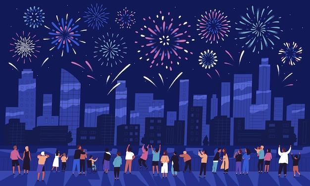 Multitud de personas viendo los fuegos artificiales en el oscuro cielo nocturno y celebrando las vacaciones contra los edificios de la ciudad