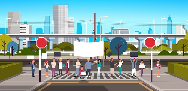 Multitud sosteniendo carteles y megáfono en el cruce de peatones