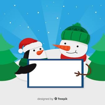 Muñeco de nieve y pingüino sosteniendo cartel vacío