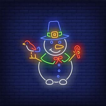 Muñeco de nieve con sombrero de bruja, con pájaro y bastón de caramelo en estilo neón