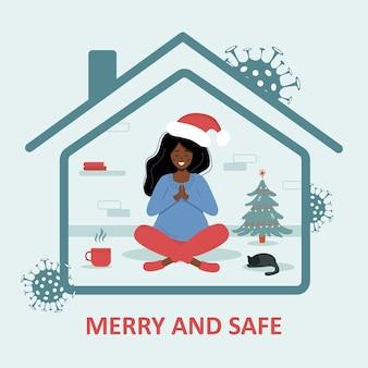 Navidad en la pandemia del covid-19. mujer africana con sombrero de santa sentada en posición de loto y celebrando la navidad. felices y seguras vacaciones.