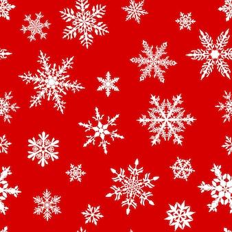 Navidad de patrones sin fisuras de complejos copos de nieve grandes y pequeños en colores blancos sobre fondo rojo.