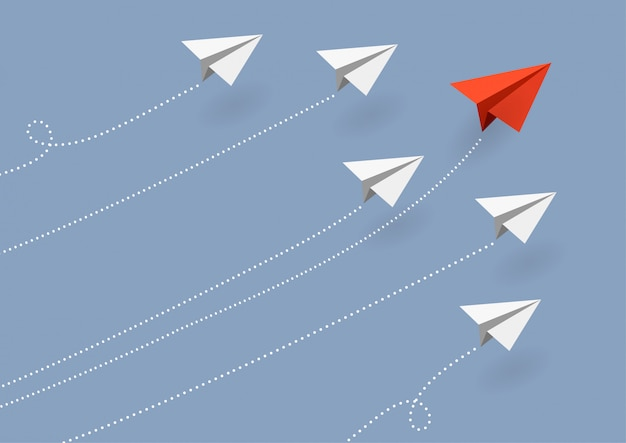 Negocio. avión de papel rojo volando cambiando de dirección en el cielo azul
