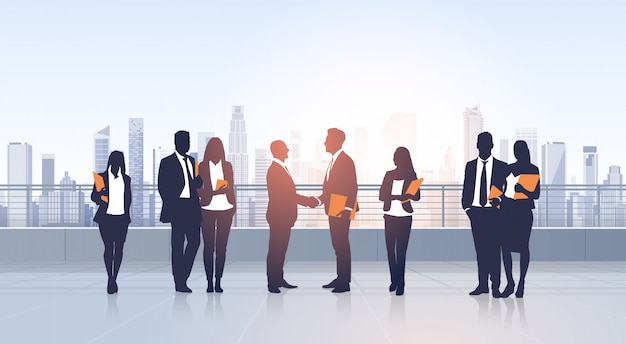 Negocio grupo de personas reunión acuerdo mano agitar siluetas moderno vista de la ciudad edificio de oficinas