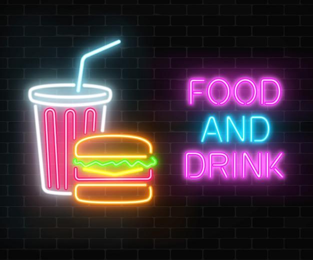 Neón comida y bebida brillante cartel en una pared de ladrillo oscuro. hamburguesa y vaso de plástico de signos de bebidas.