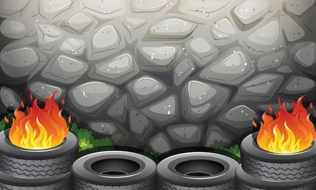Neumáticos en llamas cerca del muro de piedra