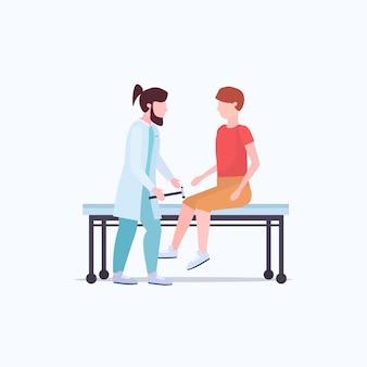 Neurólogos que prueban el reflejo de la rodilla en los médicos de rodillas del hombre en uniforme usando hummer que refleja los reflejos del concepto de salud de la medicina del paciente masculino de cuerpo entero