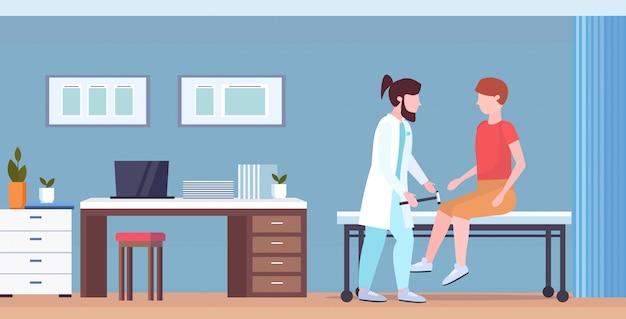 Neurólogos que prueban el reflejo de la rodilla en los médicos de rodillas del hombre en uniforme usando reflejos de control de hummer del concepto de salud de la medicina del paciente masculino interior de la oficina del hospital moderno horizontal de longitud completa