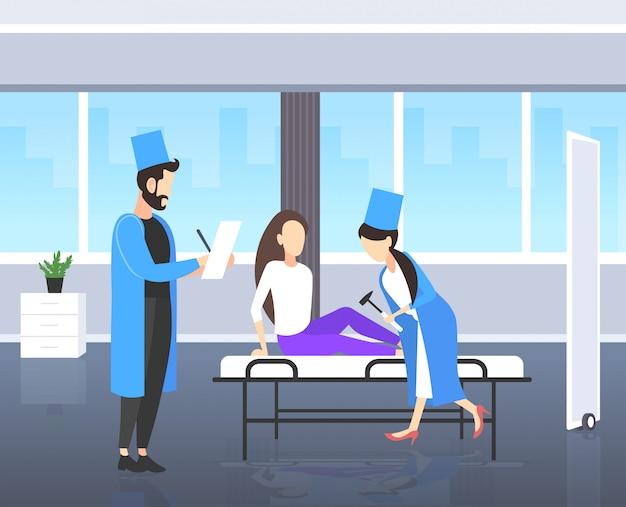 Neurólogos que prueban el reflejo de la rodilla en una mujer médicos de rodillas en uniforme usando reflejos de control de hummer del concepto de salud de la medicina del paciente femenino interior moderno de la habitación del hospital de cuerpo entero