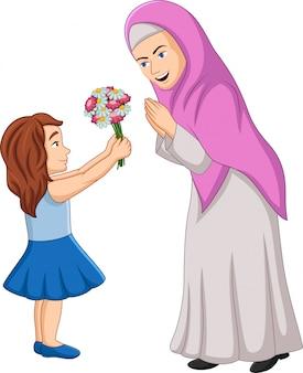 Niña dando un ramo de flores a su madre.