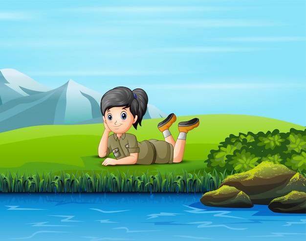 Una niña exploradora se tumbó en la hierba
