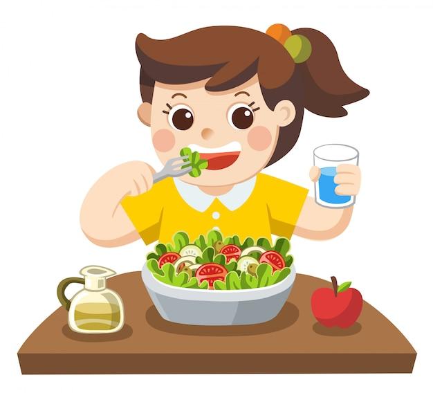 Una niña feliz de comer ensalada. a ella le encantan las verduras.