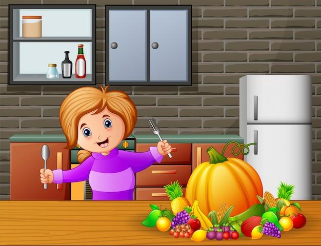 Niña feliz que sostiene la cuchara y la bifurcación que comen en la tabla