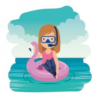 Niña con flotador flamenco y snorkel en el mar