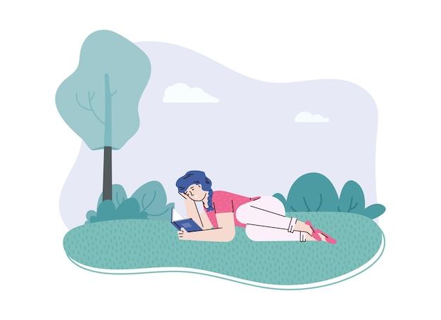 A la niña le gusta leer un libro interesante acostado sobre el césped en el parque o en la naturaleza.
