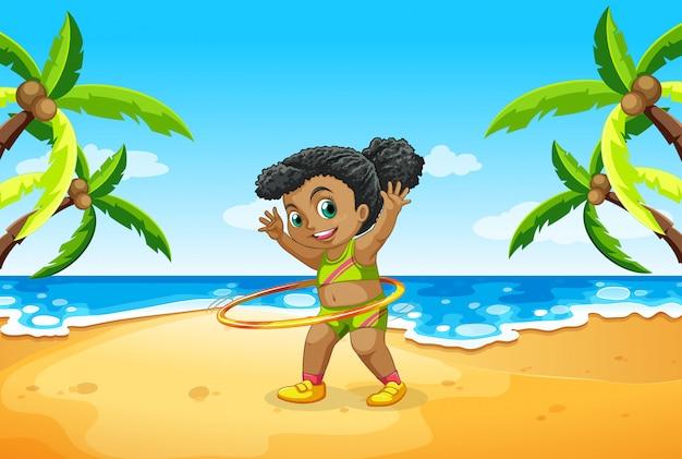 Una niña juega hula hoop en la playa.