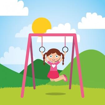 Niña jugando con anillos de la barra en el parque y día soleado