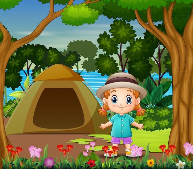 Niña linda acampando junto al paisaje del río