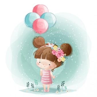 Niña linda que sostiene globos