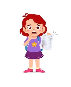 Niña linda se siente triste porque obtiene una mala calificación en el examen