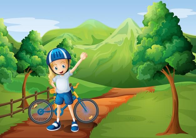 Una niña linda y su bicicleta en el camino cerca de la valla de madera