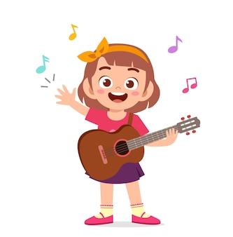 Niña linda tocar la guitarra en concierto